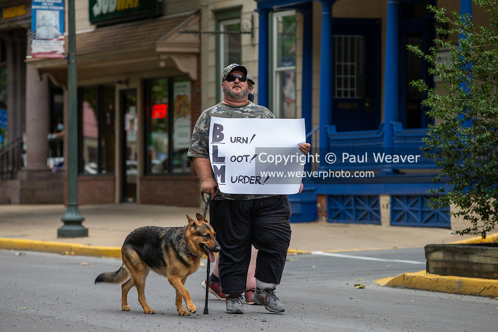 """Sunbury, PA (July 12, 2020) -- A counter-protester walks by the Sunbury Black Lives Matter protest with a dog and a sign reading """"Burn! Loot! Murder!"""" About 150 people gathered at Cameron Park in Sunbury to join the Milton-based anti-racist collective 'If Not Us, Then Who?' for a Black Lives Matter protest and march."""