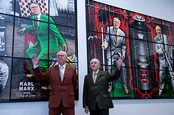 "© Licensed to London News Pictures. 12/04/2021. LONDON, UK.  Gilbert & George pose in front of ""Karl Marx"", and ""Bin Day"", both 2020, at their ""NEW NORMAL PICTURES"" exhibition at White Cube's Mason's Yard gallery in Mayfair. The exhibition displays 26 pictures from a new series the pair have been working on for over two years.  The UK government's coronavirus roadmap out of lockdown has allowed art galleries to reopen today. The exhibition runs 13 April to 8 May 2021.  Photo credit: Stephen Chung/LNP"