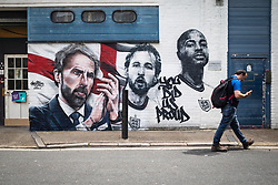 """© Licensed to London News Pictures. 14/07/2021. LONDON, UK.  A man passes a mural by urban street artists MurWalls and commissioned by Sadiq Khan, Mayor of London, which has been unveiled in Vinegar Yard near London Bridge. Featuring the slogan """"You did us proud"""", the artwork celebrates the Engalnd football team's achievement in reaching the final of Euro 2020 and features an image of manager Gareth Southgate, captain Harry Kane and forward Raheem Sterling.  Photo credit: Stephen Chung/LNP"""