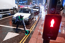 © Licensed to London News Pictures . 17/03/2017 . Cardiff , UK. A woman reaches for a hat that has blown in to the road . Revellers on a windy and wet Saint Patrick's Day night out in Cardiff city Centre . Photo credit: Joel Goodman/LNP