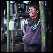 A boy laborer smiles at a metal factory in Kabul.