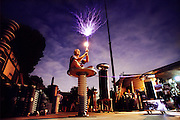 Bill Wysock in his backyard, in Monrovia (near Hollywood), California. Fiery sparks crackle from a metal tube as he also lights a 40-watt light bulb in his hands. He is sitting on a metal disk linked by a cable to his Tesla coil: a transformer producing high-frequency currents that pass safely over the surface of his body. Low-frequency currents would pass through it, meeting resistance and causing injury. MODEL RELEASED