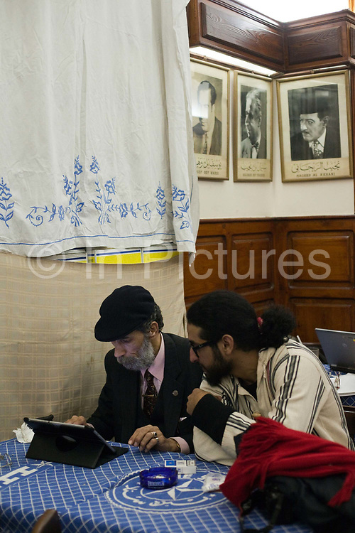 Celebrated political cartoonist Hassaneen Bassen and Murad, his young protege in conversation in the crowed Cafe Riche after a rally, Cairo, Egypt