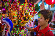 """09 FEBRUARY 2013 - BANGKOK, THAILAND:  A Chinese toy vendor sells New Year's trinkets on Yaowarat Road in Chinatown in Bangkok. Bangkok has a large Chinese emigrant population, most of whom settled in Thailand in the 18th and 19th centuries. Chinese, or Lunar, New Year is celebrated with fireworks and parades in Chinese communities throughout Thailand. The coming year will be the """"Year of the Snake"""" in the Chinese zodiac.   PHOTO BY JACK KURTZ"""