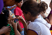Children have face paints put on before the World Cup 2014 opening game event Brazil vs Croatia outdoors in favela Do Moinho, Sao Paulo, Brazil.