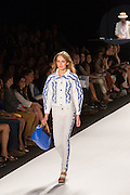 White jeans with embroidered stripes on the outside of the legs in a blue botanical design and a matching jacket.
