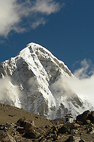 Mount Pumoti, part of the beautiful Himilayan mountain range seen on the trek to Everest base camp , looms over a stone cairn erected in memorial to a perished climber. Many cairns like this can be seen along the route to Everest.Nepal.