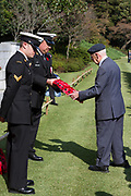 A dignitary from the Royal Airforce Association collects a wreath of poppies to lay at the Cross of Sacrifice during the Remembrance Sunday ceremony at the Hodogaya, Commonwealth War Graves Cemetery in Hodogaya, Yokohama, Kanagawa, Japan. Sunday November 11th 2018. The Hodagaya Cemetery holds the remains of more than 1500 servicemen and women, from the Commonwealth but also from Holland and the United States, who died as prisoners of war or during the Allied occupation of Japan. Each year officials from the British and Commonwealth embassies, the British Legion and the British Chamber of Commerce honour the dead at a ceremony in this beautiful cemetery. The year 2018 marks the centenary of the end of the First World War in 1918.