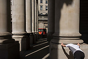 As a jogger stretches, lunchtime spring crowds enjoy warm weather beneath the pillars at Cornhill Exchange in the City of London, the heart of the capital's financial centre, dating back to first century Roman Britain. We see the classic neo-Romanesque architecture of the Royal Exchange building. At the top of Doric and Ionic columns with their ornate stonework, designed by Sir William Tite in 1842-1844 and opened in 1844 by Queen Victoria). It's the third building of the kind erected on the same site. The first Exchange erected in 1564-70 by sir Thomas Gresham but was destroyed in the great fire of 1666. It's successor, by Jarman, was also burned down in 1838. The present building is grade 1 listed and cost about £150,000.