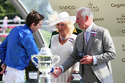 The Prince of Wales (right) and Duchess of Cornwall present jockey James Doyle with the trophy after winning the St James's Palace Stakes during day one of Royal Ascot at Ascot Racecourse.