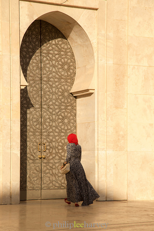 Rear view of woman wearing traditional clothing walking towards Hassan II Mosque, Casablanca, Morocco