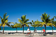 People riding bikes along the road in front of Ipanema beach, Rio de Janeiro.