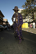 Crown Royal man Connienye Jackson strolls up Royal Street on Fat Tuesady during Mardi Gras festivities in New Orleans Tuesday feb. 28,2006. (He said to mnay bottles to count made the suit socks and all.Photo/Suzi Altman)