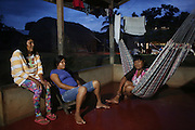 Surui, families, in their homes at night<br /><br />An Amazonian tribal chief Almir Narayamogo, leader of 1350 Surui Indians in Rondônia, near Cacaol, Brazil, with a $100,000 bounty on his head, is fighting for the survival of his people and their forest, and using the world's modern hi-tech tools; computers, smartphones, Google Earth and digital forestry surveillance. So far their fight has been very effective, leading to a most promising and novel result. In 2013, Almir Narayamogo, led his people to be the first and unique indigenous tribe in the world to manage their own REDD+ carbon project and sell carbon credits to the industrial world. By marketing the CO2 capacity of 250 000 hectares of their virgin forest, the forty year old Surui, has ensured the preservation, as well as a future of his community. <br /><br />In 2009, the four clans and 25 Surui villages voted in favour of a total moratorium on logging and the carbon credits project. <br /><br />They still face deforestation problems, such as illegal logging, and gold mining which causes pollution of their river systems