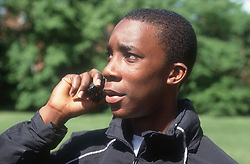 Teenage boy standing outdoors talking on mobile phone,