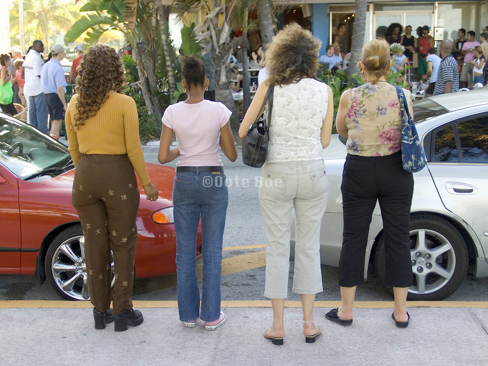 four women watching a performance across the street Collins Avenue Miami USA