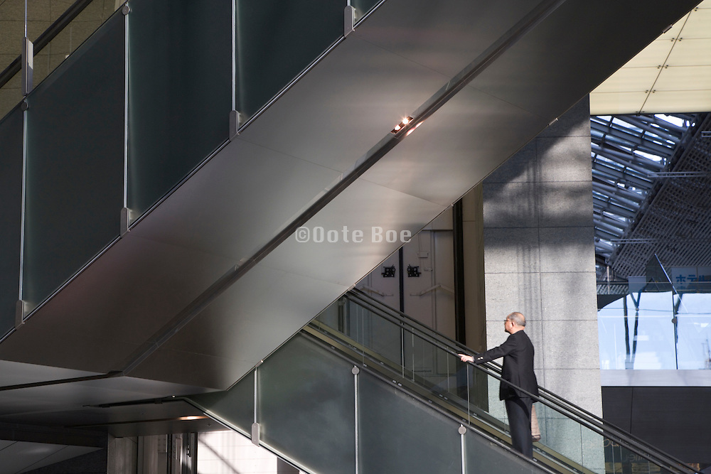 middle aged to senior businessman going up the escalator in the atrium of an modern office building