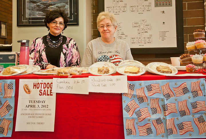 """4.3.2012  Staff member, Barb McIntire, and Volunteer, Diane Yaggi, sell hot dogs and bake goods to precenct voters in order to raise funds for the Alaska Pioneer Home """"Spirit Committee"""", downtown, Anchorage."""