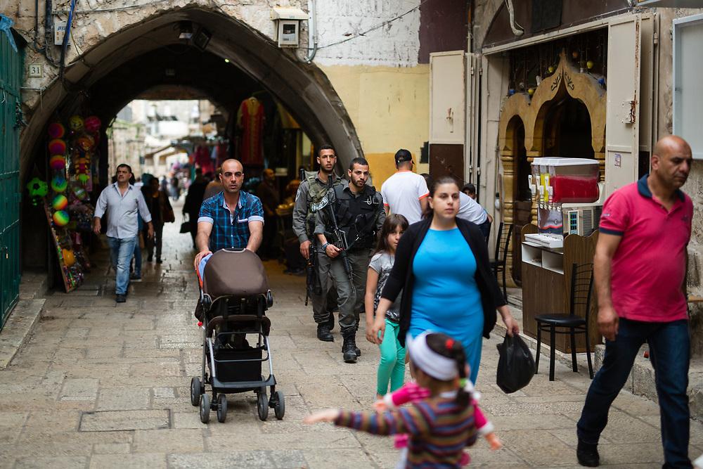 Palestinian women walk past Israeli border Police Men at HaGai Street or al Wad Street in the Muslim quarter of the Old City of Jerusalem, Israel, on April 10, 2016.