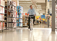 4/14/10 1:18:51 PM -- Bentonville, AR, U.S.A. -- Doug McMillon, the CEO of Walmart International, rides a bike through the Wal-Mart near the home office in Bentonville, AR for the Advice From the Top feature running Monday, April 19, 2010. -- McMillon was formerly the buyer at Wal-Mart in charge of purchasing bicycles.  ...Photo by Shane Bevel, Freelance