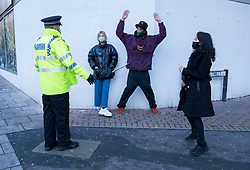 © Licensed to London News Pictures; 25/01/2021; Bristol, UK. Colston Four at court. People tell a police officer that they are exercising as the reason they are opposite the court. Defendants Rhian Graham, 29, Milo Ponsford, 25, Jake Skuse, 32, and Sage Willoughby, 21, are due before Bristol Magistrates' Court for their first hearing today. They have been charged with criminal damage in connection with damage to the statue of slave trader Edward Colston which was pulled down during a Black Lives Matter protest on June 7 2020 and then thrown into Bristol Harbour. Police launched an appeal to trace suspects after the event and ten people were located. Six people accepted a caution while four were referred to the CPS. The statue was later retrieved by Bristol City Council who say that the damage is costed at £3,750. Police have warned anyone planning to protest at the court hearing that they will be breaking the lockdown laws which prohibit public gatherings of more than two people to combat the Covid-19 coronavirus pandemic. Photo credit: Simon Chapman/LNP.