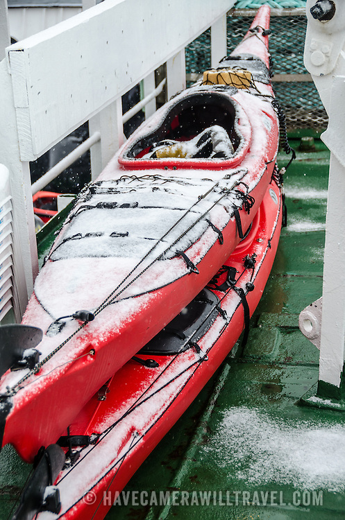 Sea kayaks on the deck of a ship are covered in fresh snow in Antarctica.