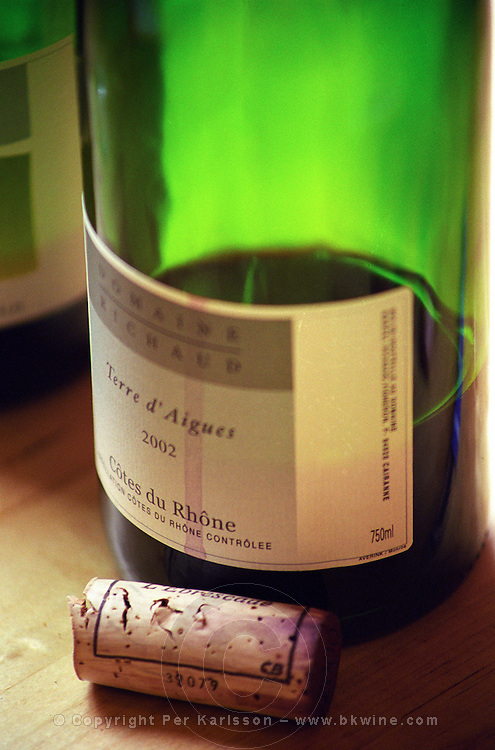 An almost empty bottle of red wine Domaine Marcel Richaud Terre d'Aigues 2002 Cotes du Rhone. A red wine streak across the label and a cork lying on the table. Domaine Marcel Richaud, Cairanne, Vaucluse, France Europe