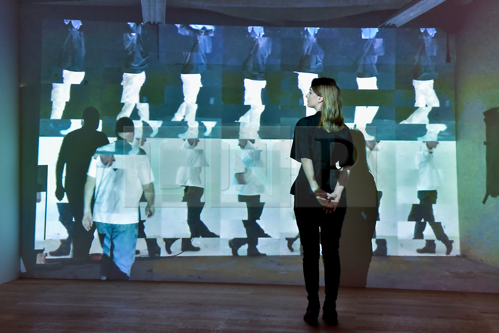 """© Licensed to London News Pictures. 31/07/2017. London, UK. A gallery staff member views """"Walk In, Walks Out"""", 2015, an HD video installation, by Bruce Nauman.  Preview of the new Artist Rooms exhibition of Bruce Nauman at Tate Modern on currently until July 2018.  Nauman is widely regarded as one of the most innovative and influential American artists working today.  The Artist Rooms gallery is the London hub for showcasing work from the Artist Rooms collection which is owned jointly by Tate and the National Galleries of Scotland.  Photo credit : Stephen Chung/LNP"""