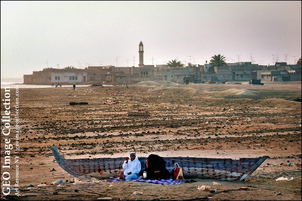 """On Muharraq Island, the largest island in the Archipelago of Bahrain, a couple picnic in the shade of a traditional wooden fishing boat on Friday, the Islamic holy day devoted to worship, relaxation, and family.  The woman is covered in a black cloak known in the Persian or Arabian Gulf countries as a """"abaya."""""""