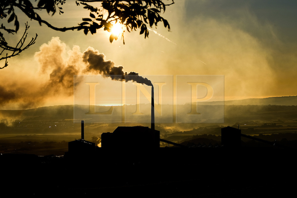 © Licensed to London News Pictures.02/10/15<br /> Staithes, UK. <br /> <br /> Smoke rises from a chimney at a potash mine as dawn breaks over the North Yorkshire village of Staithes on the east coast as the warm autumn weather continues.<br /> <br /> Photo credit : Ian Forsyth/LNP