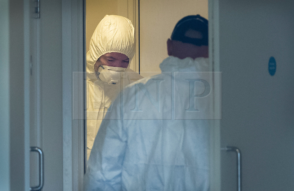 © Licensed to London News Pictures. 05/01/2019. Farnham, UK. Police forensics officers searches in the hallway of a property in Farnham, Surrey after a couple were arrested in connection with the murder of a man on a train yesterday. A murder investigation has been launched after the man was attacked while on board the 12. 58pm train service travelling between Guildford and London Waterloo. A man and a woman have been detained by police in Farnham in connection with the murder. Photo credit: Peter Macdiarmid/LNP