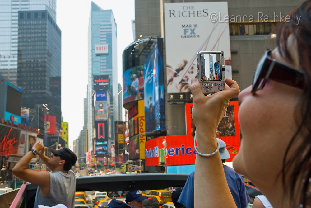 Tourists photograph Times Square continuously during the summer months in downtown Manhattan, New York City, NY, USA.