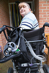 Woman who has severe asthma with oxygen cylinder and tubes attached turning around in wheelchair whilst entering her front door,