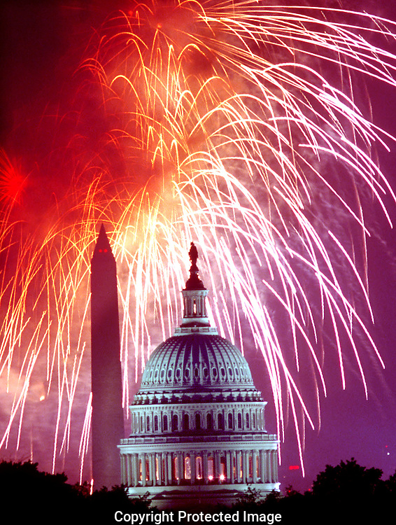 A 15.8 MG IMAGE OF:.Fireworks celebrate the Forth of July on the Mall with the  U.S. Capitol in the foreground and the Washington Monument behind.  Photo by Dennis Brack.Note: this is a real photo--not a composite