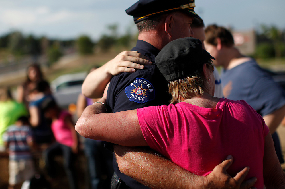 Aurora Colorado Chief of Police Dan Oates poses for a photo with citizens at the memorial to the movie theater shooting victims in Aurora July 25, 2012. First responders got their first look at the growing memorial today.   REUTERS/Rick Wilking (UNITED STATES)