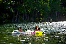 Stock photo of three women floating down the Frio River on a hot afternoon in the Texas Hill Country, Uvalde County in Garner State Park