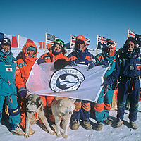 Members of the 1989-1990 Trans-Antarctica Expedition pose for pictures at the ceremonial South Pole.  From left to right: Keizo Funatsu (Japan), Jean-Louis Etienne (France), Will Steger (USA), Qin Dahe (China), Geoff Somers (UK), and Victor Boyarsky (USSR).