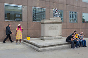 A lady smokes a cigarette and tourists pose for a selfie at the City of London boundary griffin at the southern Southwark end of London Bridge, on 30th May 2018, in London, England.