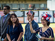 04 JULY 2019  - DES MOINES, IOWA: MJ VENTURA LIBANAN, originally from the Philippines, waves an American flag just before she took of citizenship to become a naturalized American citizen. Thirty people became US citizens during a naturalization ceremony at the Iowa Cubs game in Des Moines. The naturalization ceremony is an Iowa Cubs 4th of July tradition. This is the 11th year they've held the ceremony.           PHOTO BY JACK KURTZ