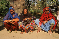 Group of three women sitting by the side of the road in Delhi; India; one of them knitting,