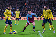 Aaron Cresswell (West Ham) & Ainsley Maitland-Niles (Arsenal) waits to see Lucas Torreira (Arsenal) kick the ball during the Premier League match between West Ham United and Arsenal at the London Stadium, London, England on 9 December 2019.