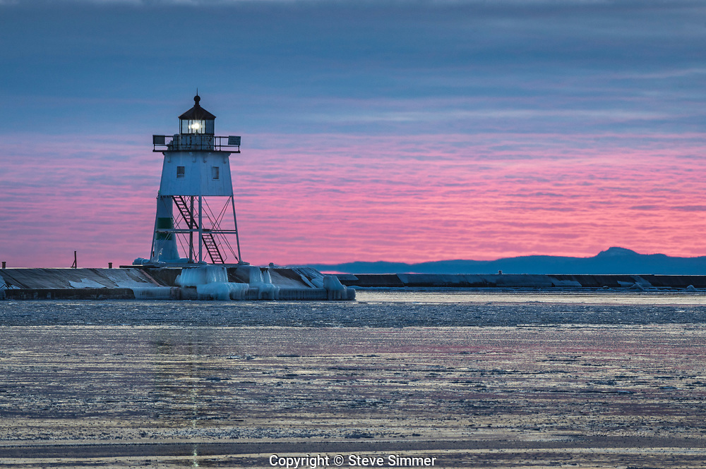 I have learned to never give up on a sunset until 20 minutes after the sun goes below the horizon. This is one reason why. When high clouds reach almost to the horizon, but not beyond it, the sun can reach up to illuminate those clouds from below. Colors are intense, but only for a few seconds. It is good to be ready! Harbor Lighthouse, Grand Marais, MN