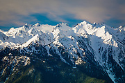 The Olympic Mountains is a mountain range on the Olympic Peninsula of western Washington in the United States. The mountains, part of the Pacific Coast Ranges, are not especially high - Mount Olympus is the highest at 7,962 ft (2,427 m) - but the western slopes of the Olympics rise directly out of the Pacific Ocean and are the wettest place in the 48 contiguous states. On the wetter end of the spectrum, 140 and 170 inches (3,600 and 4,300 mm) of rain falls on the Hoh Rainforest annually. Conversely, areas to the northeast of the mountains are located in a rain shadow and receive as little as 16 in (410 mm) of precipitation. Most of the mountains are protected within the bounds of the Olympic National Park. Physiographically, they are a section of the larger Pacific Border province, which is in turn a part of the larger Pacific Mountain System.