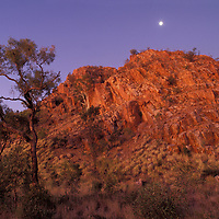 Australia, Northern Territory, Moon rises above red cliffs near Outback town of Alice Springs