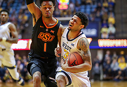 Jan 12, 2019; Morgantown, WV, USA; West Virginia Mountaineers guard James Bolden (3) drives against Oklahoma State Cowboys guard Curtis Jones (1) during the second half at WVU Coliseum. Mandatory Credit: Ben Queen-USA TODAY Sports