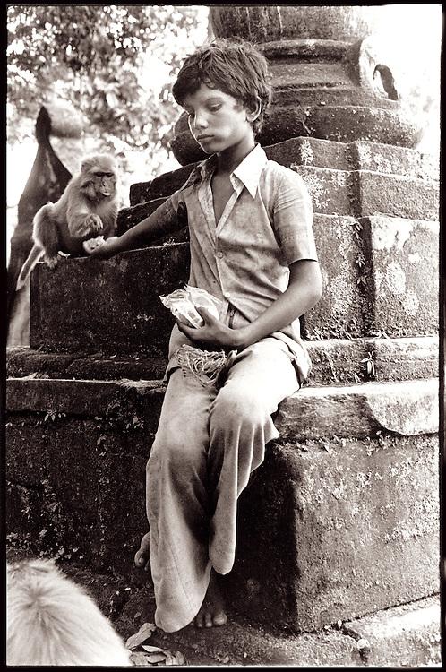 Sepia-toned, black and white image of a boy feeding the sacred monkeys at Swyambhunath, the Monkey Temple, on wooded hill overlooking Nepal's Kathmandu Valley