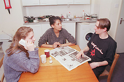 Teenagers sitting around table in hostel kitchen talking and using telephone,