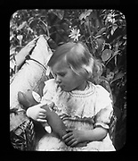 Halftone portrait photograph of young girl holding and looking at her cuddly toy c 1900