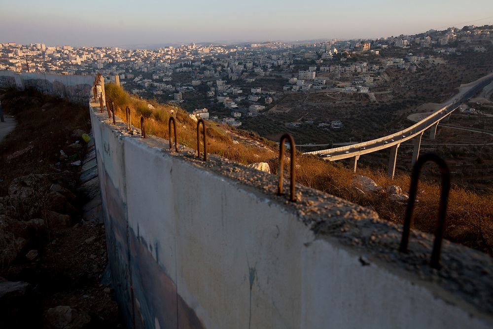 The Palestinian village of Beit Jalla (L) and a section of Highway 60 exiting Jerusalem (R), are seen behind a section of the Gilo protective wall in Jerusalem, on August 12, 2010. On Sunday, August 15, the IDF will begin to dismantle the wall which protected the residents of Gilo neighborhood in Jerusalem, from gunfire and mortar shells. The wall was put up in 2001, during the Second Intifada, when Gilo came under intense near daily attacks from the adjacent Arab village of Beit Jalla, which had been handed over to the Palestinian Authority under Yasser Arafat, as part of the Oslo Accords. The IDF stated that the decision to remove the wall was preceded by a security assessment at Central Command which determined that the move was a safe one.