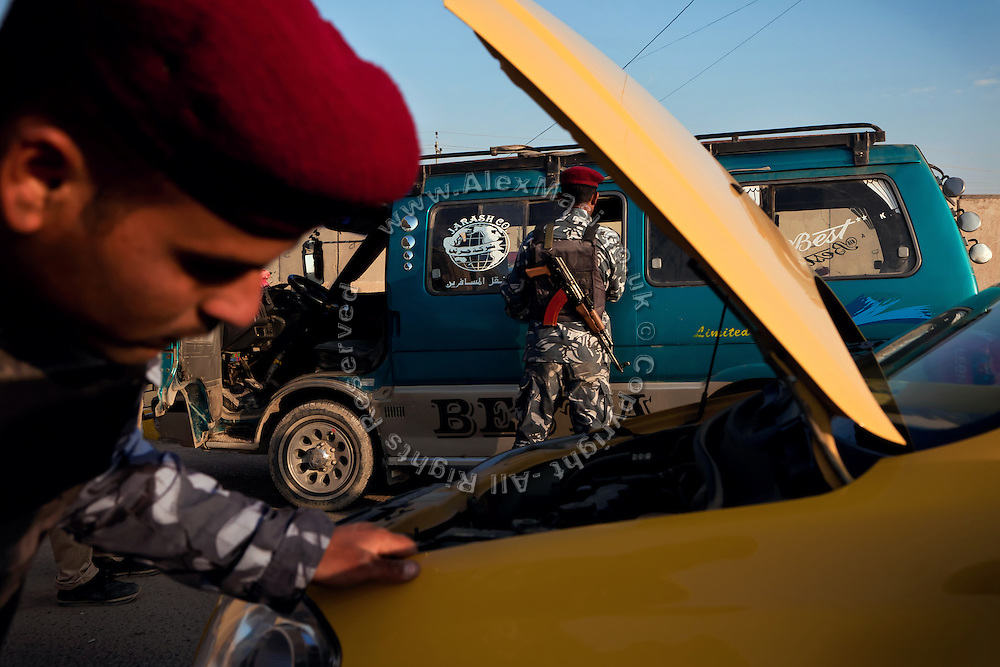 Members of the Iraqi Police are checking vehicles passing through the main checkpoint to the city of Fallujah, Iraq, on the Highway N.10. (Baghdad-Fallujah-Ramadi)